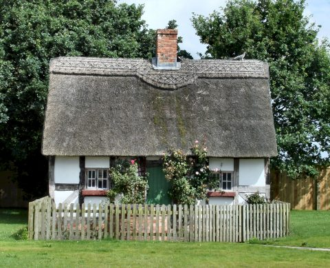Black and white thatched cottage with a picket fence to the front