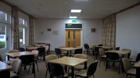 View of the Village Hall Lounge from the main entrance hall laid out with tables and chairs